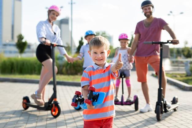 Gelukkige familie rijdt op elektrische scooters en gyroscuters in het park, op de voorgrond houdt een kleine jongen een schaats in zijn handen en steekt een duim omhoog