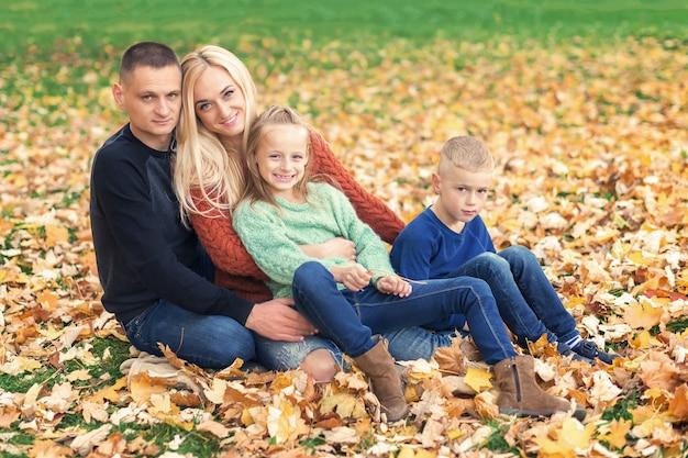 Gelukkige familie rusten in prachtige herfst park