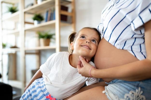Gelukkige familie, saamhorigheid, liefde. mooie zwangere moeder met schattig kind