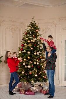 Gelukkige familie samen de kerstboom binnenshuis versieren