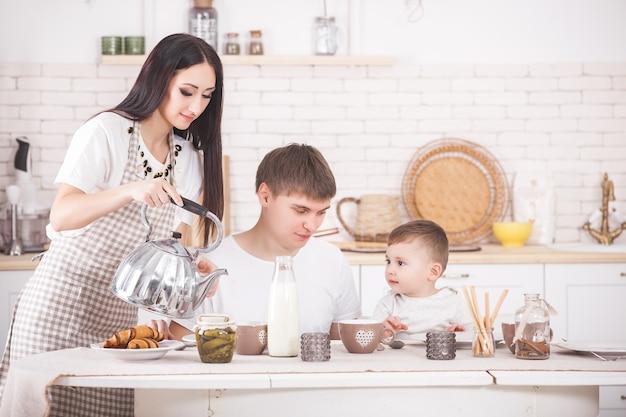 Gelukkige familie samen ontbijten. jong gezin eten aan de tafel op de keuken. moeder, vader en kleine baby eten.