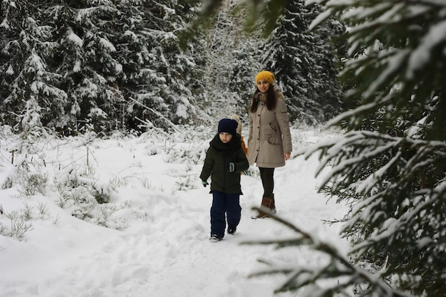 Gelukkige familie spelen en lachen in de winter buiten in de sneeuw. stadspark winterdag.