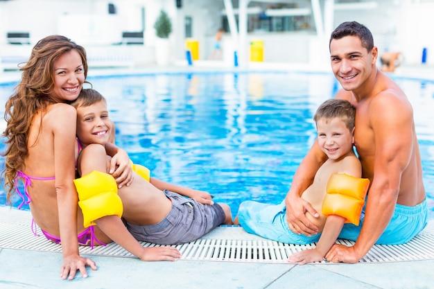 Gelukkige familie spelen in het zwembad. zomer vakantie concept