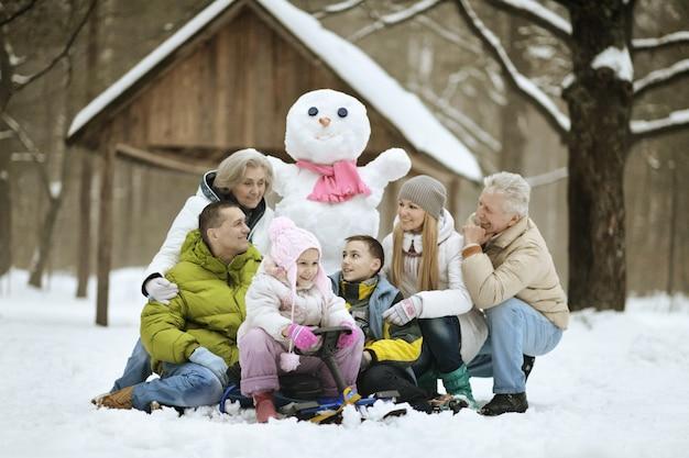 Gelukkige familie spelen in verse sneeuw en sneeuwpop bouwen op mooie zonnige winterdag buiten in de natuur