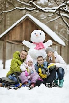 Gelukkige familie spelen in verse sneeuw en sneeuwpop op mooie zonnige winterdag buiten in de natuur