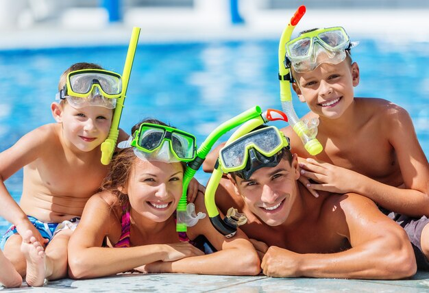 Gelukkige familie spelen in zwembad. zomer vakantie concept