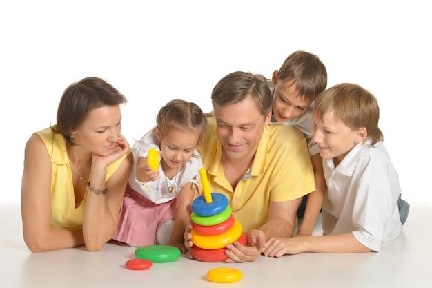 Gelukkige familie spelen met speelgoed, geïsoleerd op wit