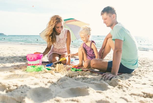 Gelukkige familie spelen op het strand en bouwen een zandkasteel