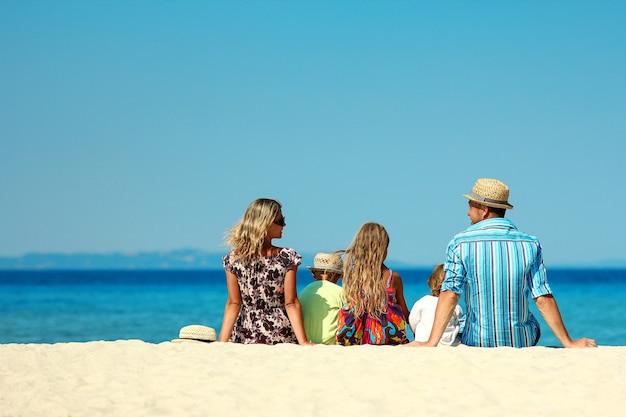 Gelukkige familie spelen op het strand in de buurt van de blauwe zee op zomervakantie