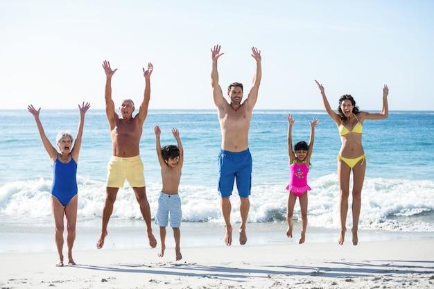 Gelukkige familie springen op het strand