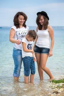 Gelukkige familie staande op een houten ponton voor de zee in de zomer