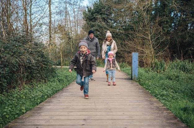 Gelukkige familie staande over een houten pad terwijl kind op de voorgrond loopt. selectieve focus op familie.