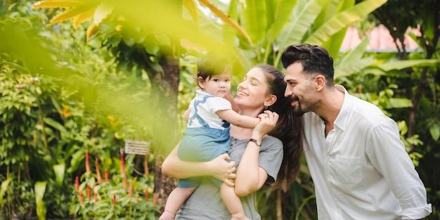 Gelukkige familie thuis samen concept, kinderen vreugde met vader en moeder op zomer natuurtuin buiten, mensen die plezier hebben, jongen of meisje en jonge vrouw lachen levensstijl buiten het park