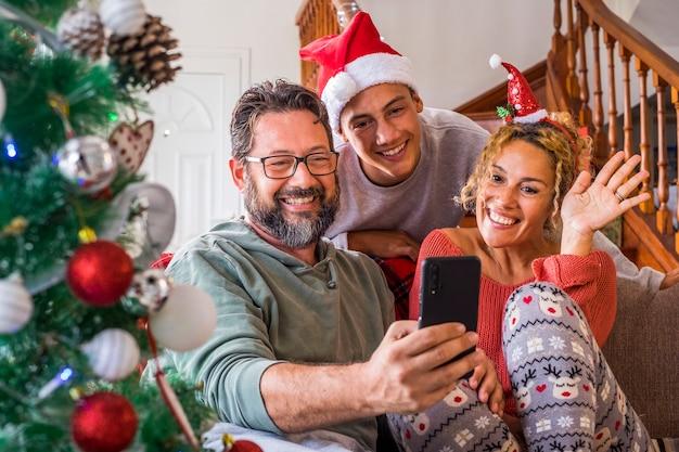 Gelukkige familie thuis tijdens kerstavond geniet van een videogesprek met vrienden en ouders