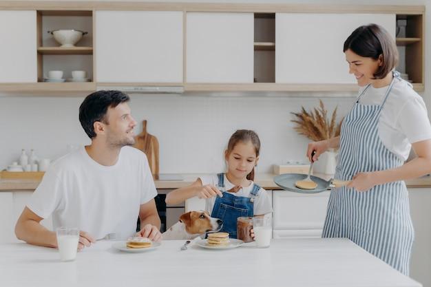 Gelukkige familie tijd en ontbijt concept. vrolijke vrouw en moeder bereiden heerlijke pannenkoeken voor familieleden, vader, dochter en hond genieten van eten en proeven van dessert thuis, voegen chocolade toe