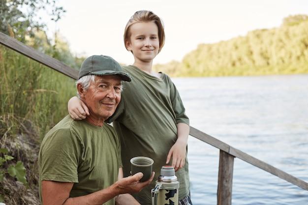 Gelukkige familie tijd samen doorbrengen buiten. vader en zoon zittend op houten plaatsing in de buurt van water, warme drank drinken, jongen zijn vader knuffelen.