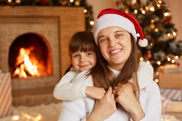 Gelukkige familie tijd samen doorbrengen, moeder en haar dochtertje knuffelen terwijl ze op de vloer zitten in een feestelijke woonkamer met open haard en kerstboom.