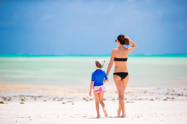 Gelukkige familie tijdens de zomervakantie op wit strand