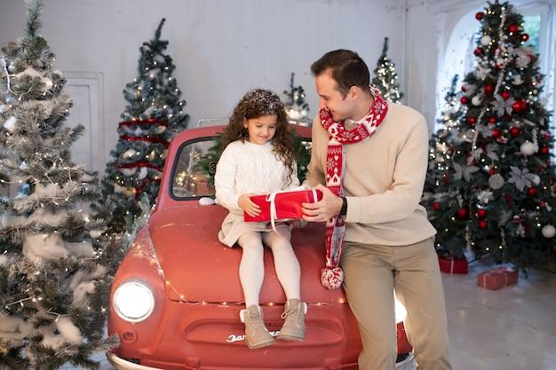 Gelukkige familie, vader die de doos van de de gift van zijn dochter geeft dichtbij de kerstboom en de rode auto.