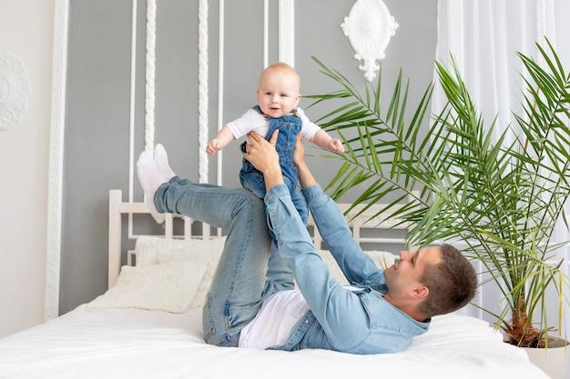 Gelukkige familie vader en baby spelen en knuffelen op het bed