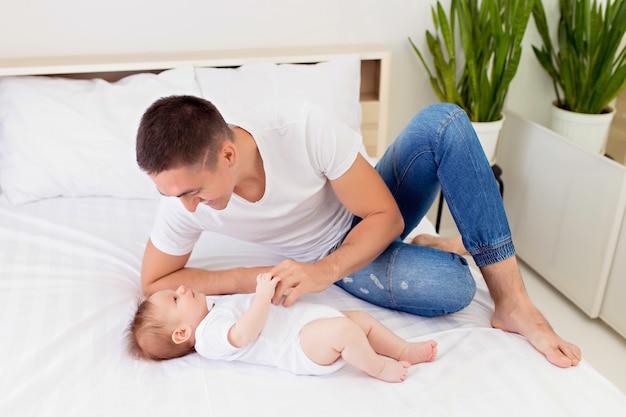 Gelukkige familie: vader en zoon jongen spelen op een wit bed in een zonnige slaapkamer.