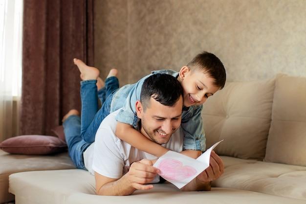 Gelukkige familie, vader en zoon liggen op de bank.