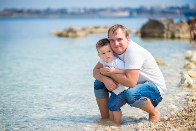 Gelukkige familie vader en zoon staan op een houten ponton voor de zee in de zomer.