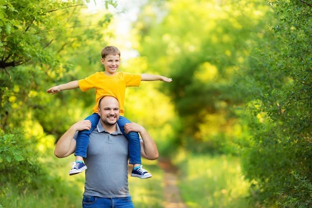 Gelukkige familie: vader en zoon wandelen in de natuur in de zomer. de zoon zit op de rug van zijn vader.