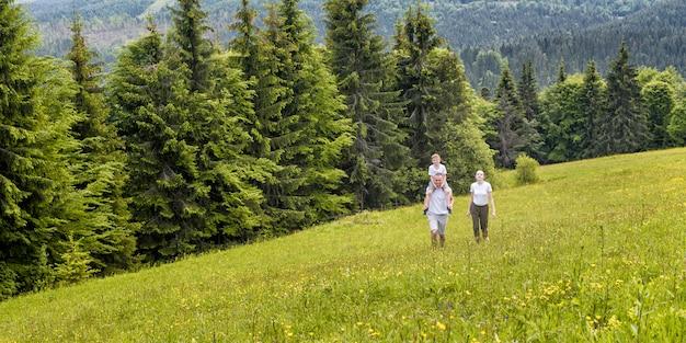 Gelukkige familie: vader met zoon op schouders en moeder gaan op een groen veld