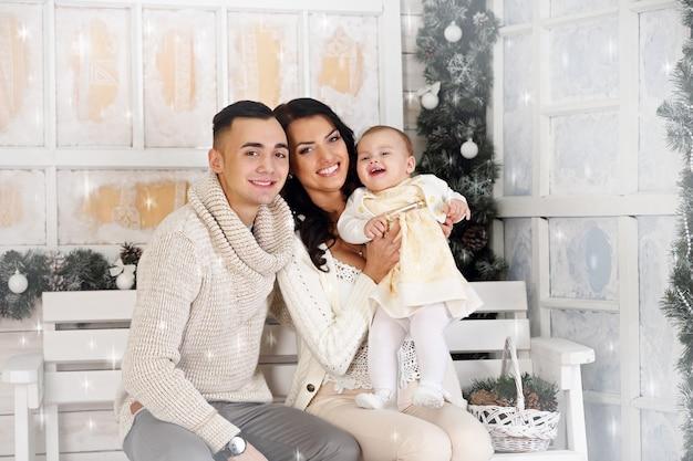 Gelukkige familie, vader, moeder en dochter op de veranda met kerstversiering