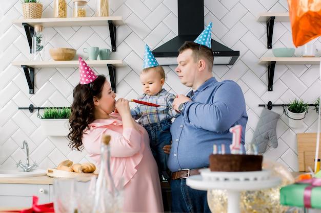 Gelukkige familie, vader, moeder en kleine babyjongen blazen in partij hoorns op verjaardagsfeestje thuis. portret van ouders die weinig de eerste verjaardag van hun zoon vieren