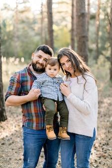 Gelukkige familie, vader, moeder en zoontje, stijlvolle casual kleding dragen, wandelen in het dennenbos van de herfst op een mooie zonnige dag