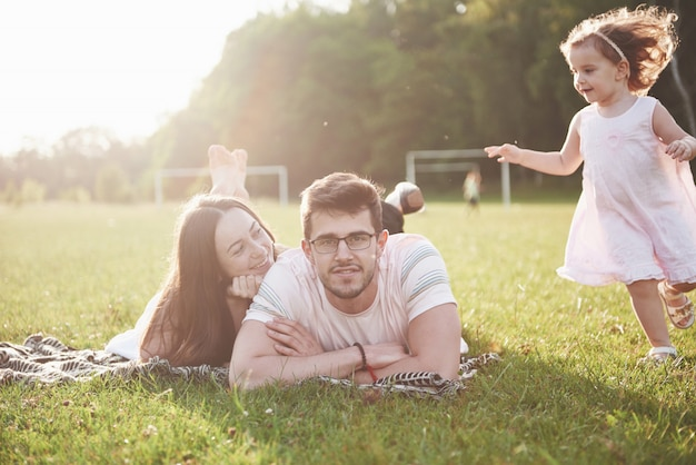 Gelukkige familie, vader van moeder en dochter van baby in de natuur bij zonsondergang