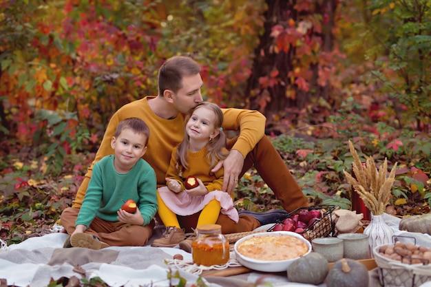 Gelukkige familie vader, zoontje, dochter op herfstpicknick met cake, pompoen, thee