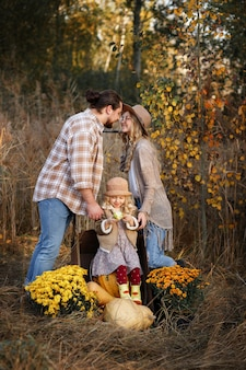 Gelukkige familie van boeren met pompoenen in de herfst