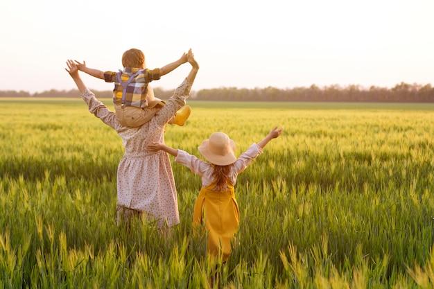 Gelukkige familie van boeren, vader, moeder, zoon en meisje in strohoed op tarweveld bij zonsondergang.