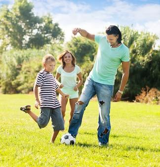 Gelukkige familie van drie spelen met bal