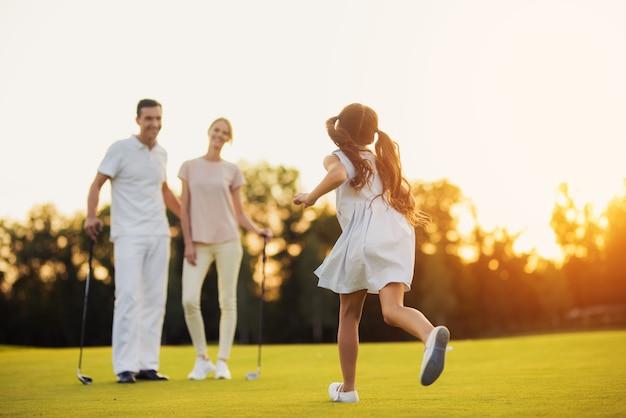 Gelukkige familie van golfspelers op een groene weide.