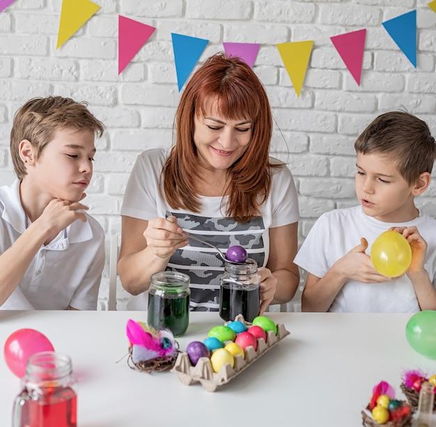 Gelukkige familie van moeder en twee jongens opblazen van de ballonnen