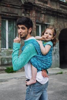 Gelukkige familie van vader en babymeisje zitten in draagdoekrugzak