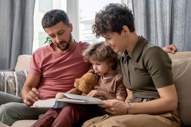 Gelukkige familie van vader, moeder en zoontje met teddy leesboek met verhalen zittend op een comfortabele bank bij raam in de woonkamer
