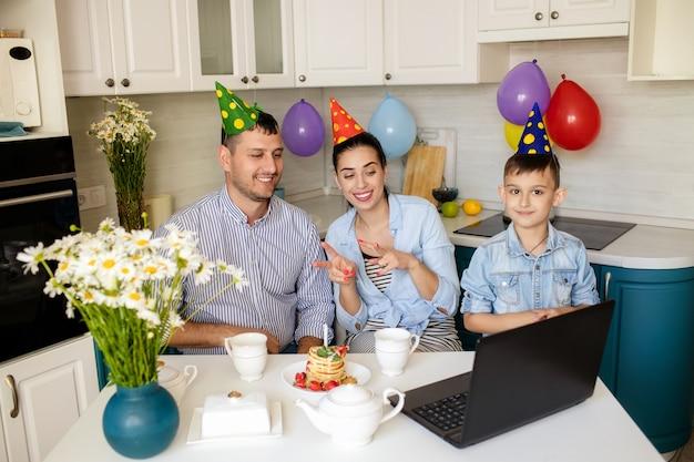 Gelukkige familie vieren een verjaardag thuis in de keuken en online chatten op een laptop