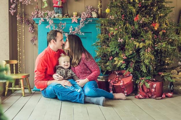 Gelukkige familie viert kerstmis. moeder, vader en zoon n achtergrond kerstboom