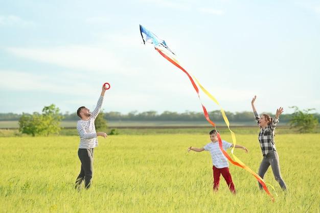 Gelukkige familie vliegende vlieger in het veld