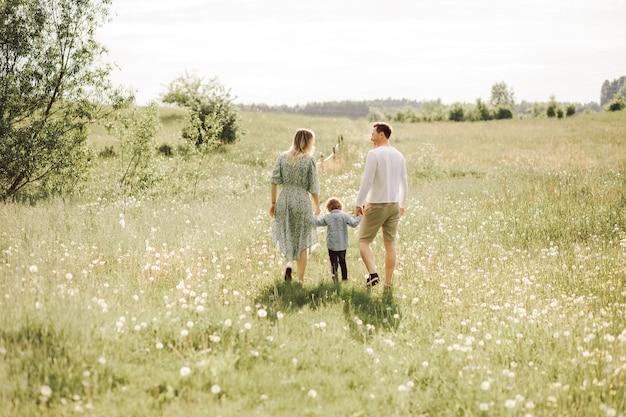 Gelukkige familie wandelen in de weide van bloeiende bloemen van achteren, vader moeder en zoon, achteraanzicht foto
