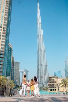 Gelukkige familie wandelen in dubai met burj khalifa wolkenkrabber op de achtergrond.