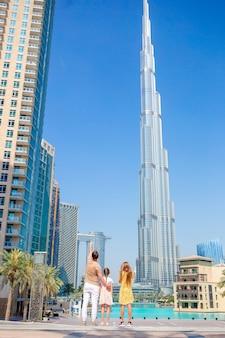 Gelukkige familie wandelen in dubai met burj khalifa wolkenkrabber