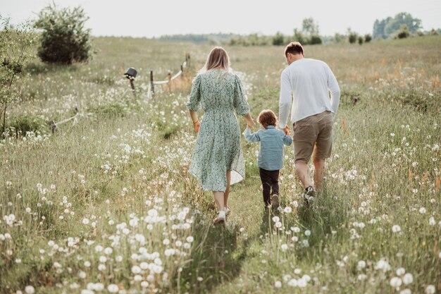 Gelukkige familie wandelen in het veld van bloeiende bloemen van achteren, vader, moeder en zoon