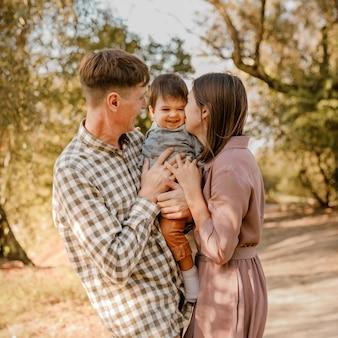 Gelukkige familie wandelen op de weg in het park vader moeder bedrijf zoontje op handen en samen gaan