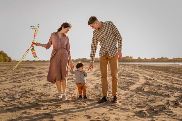 Gelukkige familie wandelen op het zandstrand van de rivier. vader, moeder die zoontje op handen houdt en met vlieger speelt.